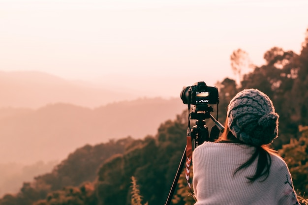Fotógrafo da jovem mulher que toma a imagem da paisagem quando nascer do sol no pico de montanha.