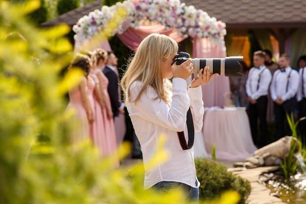 Fotógrafo de casamento com uma câmera profissional que trabalha em uma cerimônia de casamento