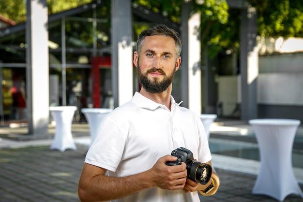 Fotógrafo de casamento de evento com câmera nas mãos, barba e sorriso