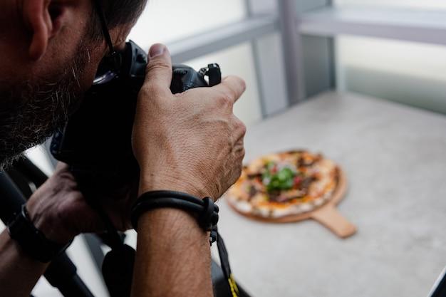 Fotógrafo de comida tirando fotos de pizza