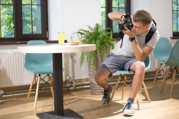 Fotógrafo de homem com câmera slr digital tira fotos de comida em um café fotografia de comida nos bastidores