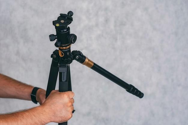 Fotógrafo de homem segura um tripé profissional nas mãos para tirar fotos e gravar vídeos.