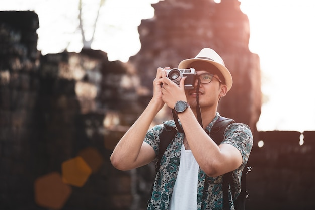 Fotógrafo de homem viajante com mochila, tirando foto com sua câmera de filme retrô