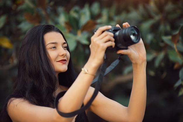Fotógrafo de mulher atraente tirando fotos com a câmera dslr ao ar livre no parque. lindo feliz