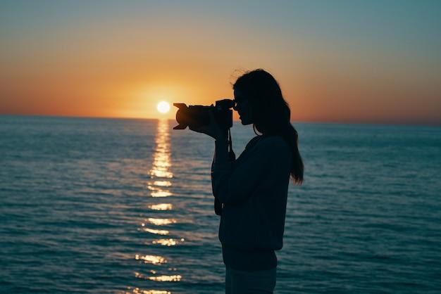Fotógrafo de mulher com câmera ao pôr do sol perto do mar na praia. foto de alta qualidade