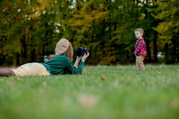 Fotógrafo de mulher fotografando a criança no parque