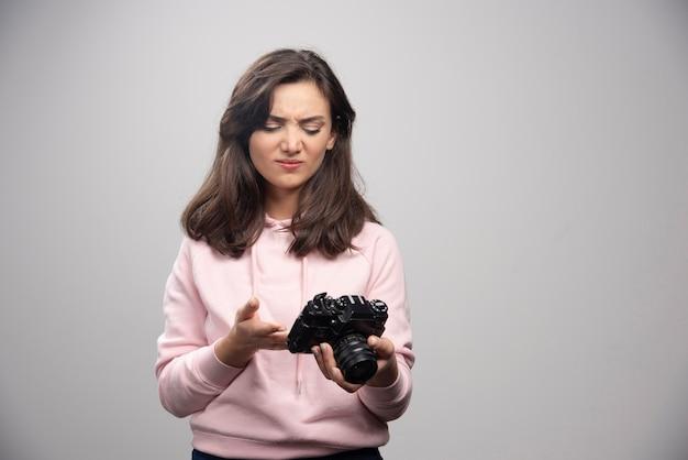 Fotógrafo de mulher olhando fotos na câmera.