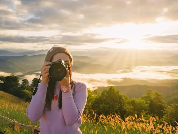 Fotógrafo de mulher segurando uma câmera na natureza