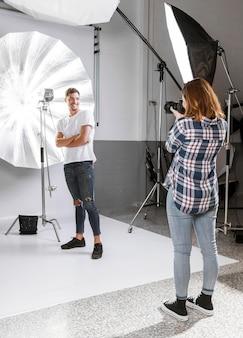 Fotógrafo de mulher tirando fotos do modelo