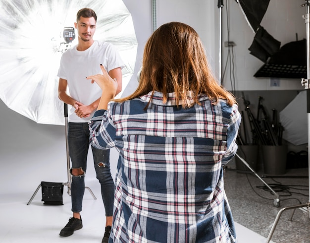 Fotógrafo de mulher tirando uma foto do modelo masculino