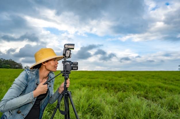 Fotógrafo de mulher tirar foto na natureza de colinas