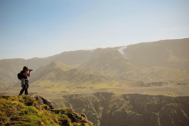 Fotógrafo de natureza com câmera digital no topo da montanha