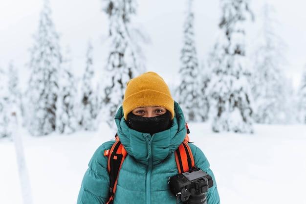 Fotógrafo de paisagens em uma floresta de neve