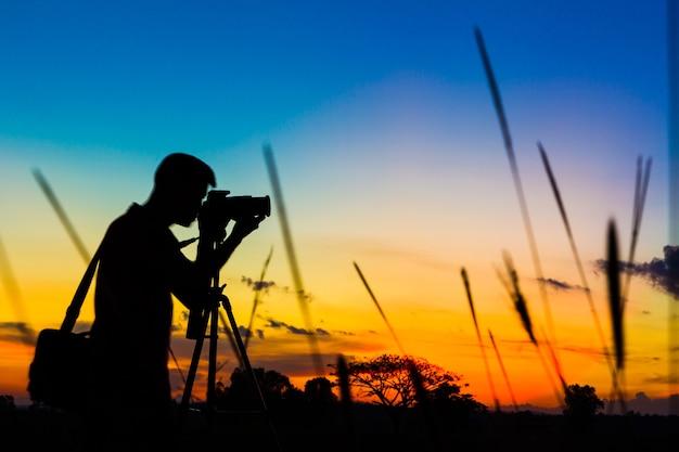 Fotógrafo de silhueta com fundo por do sol