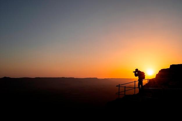 Fotógrafo de silhueta que fotografa um pôr do sol nas montanhas. conceito de fotógrafo