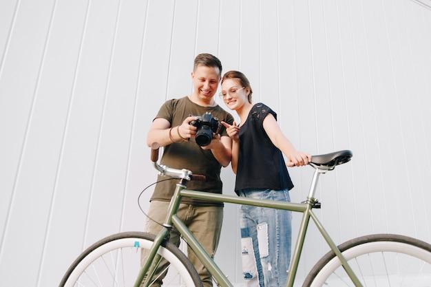 Fotógrafo de sorriso e mulher feliz que verificam fotos após a sessão fotográfica, estando com a bicicleta retro sobre a parede branca. ao ar livre.