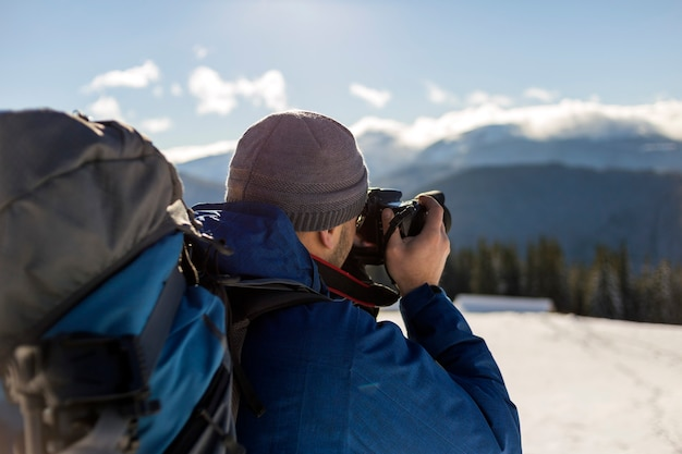 Fotógrafo de turista homem caminhante em roupas quentes com mochila e câmera tirando foto de vale nevado e paisagem de picos de montanha arborizada sob o céu azul em dia frio de inverno ensolarado.