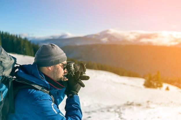 Fotógrafo de turista homem caminhante em roupas quentes com mochila e câmera tirando foto de vale nevado e paisagem de picos de montanha arborizada sob o céu azul em um dia frio de inverno ensolarado.