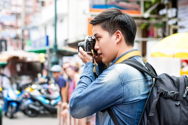 Fotógrafo de turista masculino asiático tirando foto na estrada de khao san na cidade de bangkok