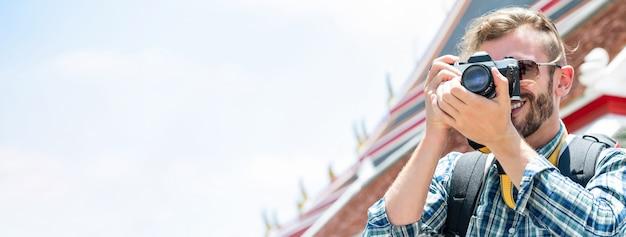 Fotógrafo de turista masculino tirando foto com a câmera enquanto viaja em bangkok tailândia