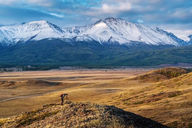 Fotógrafo de viagem no topo de uma colina na estepe kurai, vista da cordilheira norte chuysky altai rússia