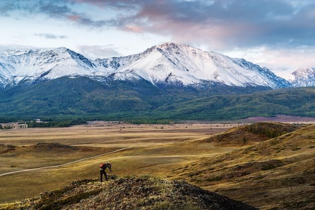 Fotógrafo de viagem no topo de uma colina na estepe kurai, vista do cume north chuysky. distrito kosh-agachsky, república de altai, rússia