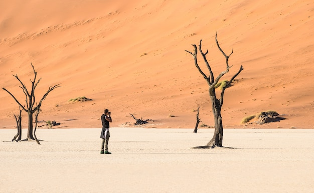 Fotógrafo de viagens de aventura na cratera deadvlei em sossusvlei namíbia