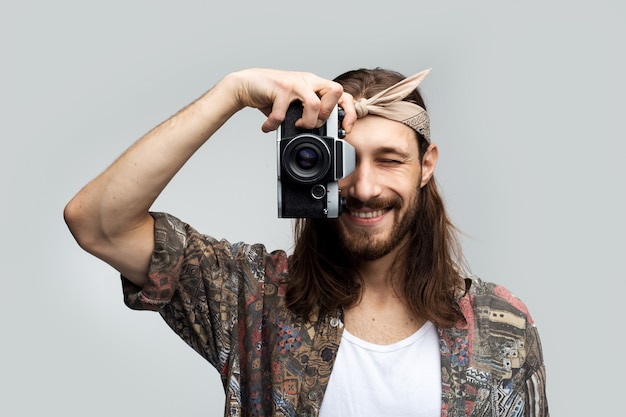 Fotógrafo de viagens elegante homem feliz com cabelos longos e um curativo na cabeça fotografa em uma câmera de filme e sorri enquanto olha através da lente de uma lente em um fundo branco do estúdio