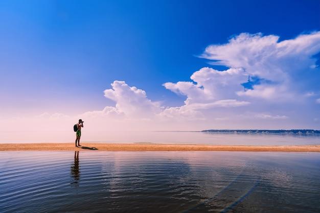 Fotógrafo de viajante com mochila, tirando fotos do mar em repouso