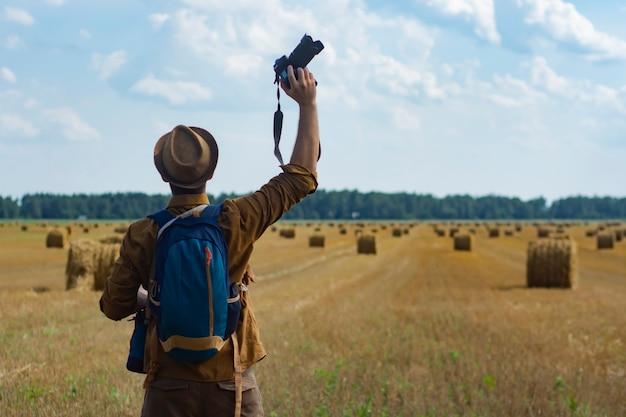 Fotógrafo de viajante com uma câmera na mão no contexto de um campo e montes de feno.