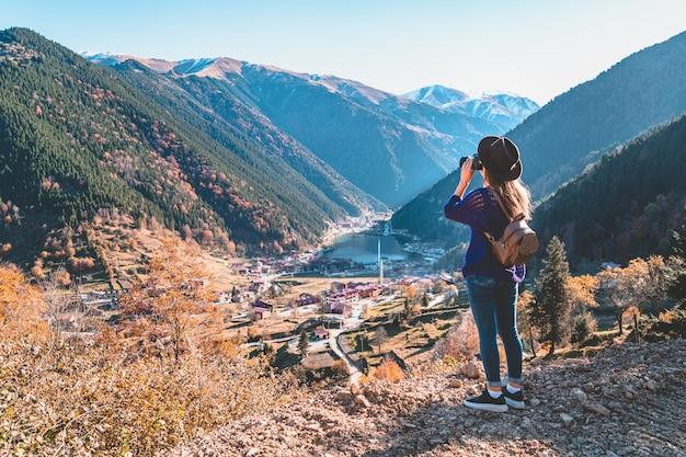 Fotógrafo de viajante de mulher na moda hipster elegante em um chapéu de feltro com mochila marrom tirando fotos das montanhas e do lago uzungol em trabzon durante a viagem à turquia