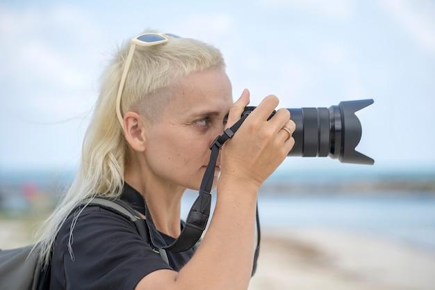 Fotógrafo de viajante turístico tirando fotos da paisagem na câmera fotográfica, garota hippie com mochila, apreciando a bela paisagem do mar. retrato de jovem loira com mochila na praia de perto