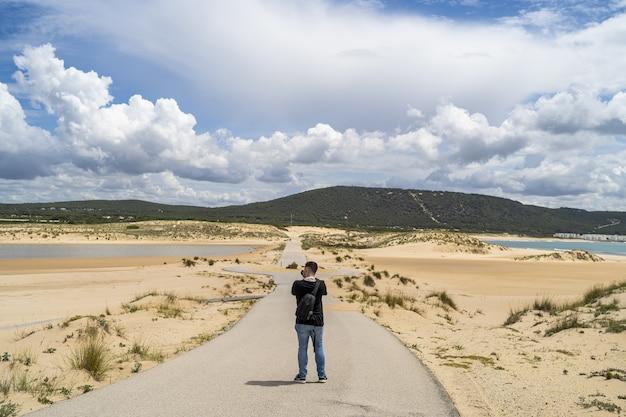 Fotógrafo do sexo masculino caminhando por uma praia sob um céu nublado durante o dia na andaluzia, espanha
