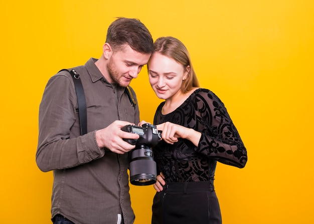 Fotógrafo e modelo verificando fotos na câmera