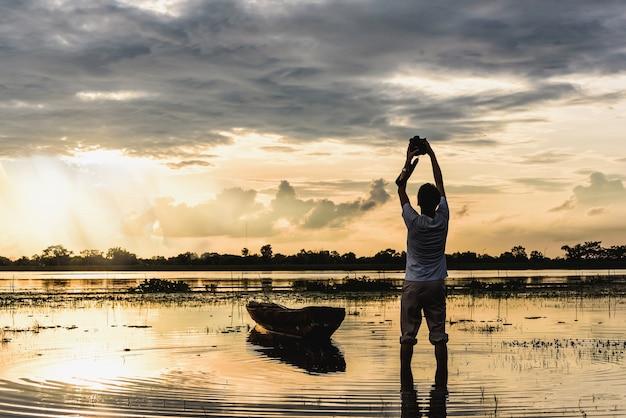 Fotógrafo em pé na frente do barco durante a captura de momento do sol paisagem