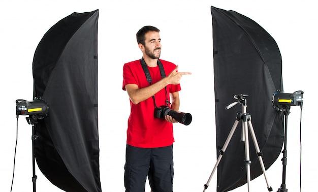 Fotógrafo em seu estúdio apontando para o lateral
