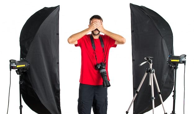 Fotógrafo em seu estúdio cobrindo os olhos