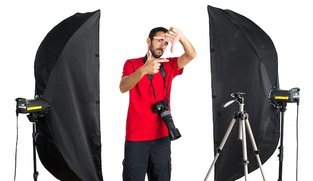 Fotógrafo em seu estúdio, concentrando-se com os dedos