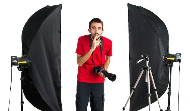 Fotógrafo em seu estúdio fazendo gesto de silêncio
