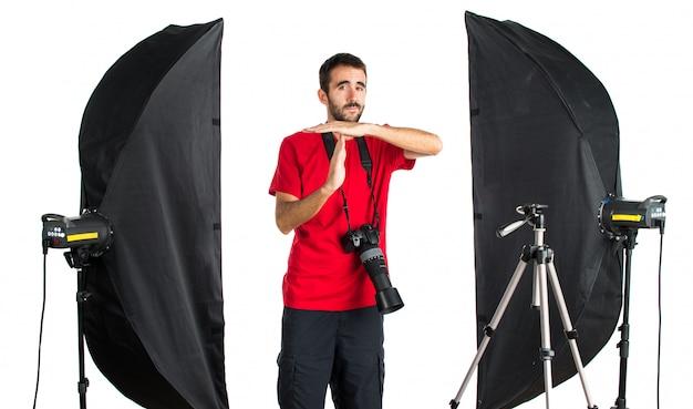 Fotógrafo em seu estúdio fazendo gesto de tempo