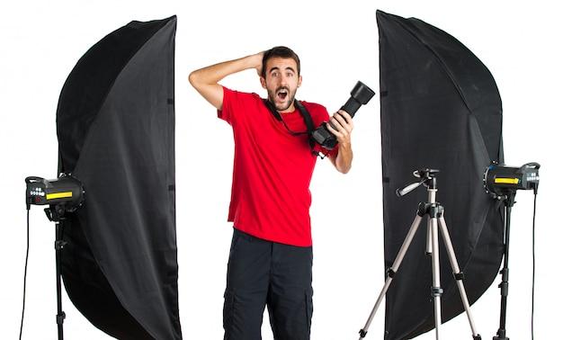 Fotógrafo em seu estúdio fazendo gesto surpresa