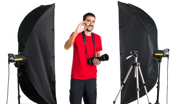 Fotógrafo em seu estúdio fazendo sinal de ok