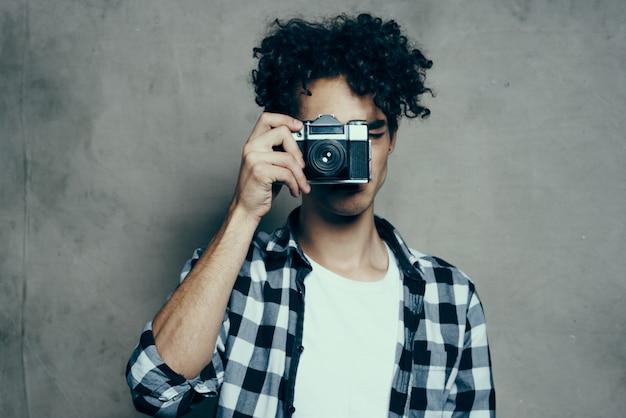 Fotógrafo em uma camisa xadrez com uma câmera na mão em um fundo cinza em uma sala de estúdio de hobby