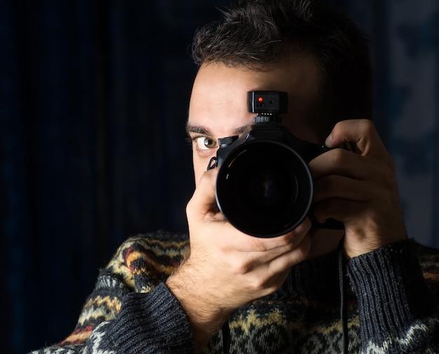 Fotógrafo está usando sua câmera profissional para tirar uma selfie