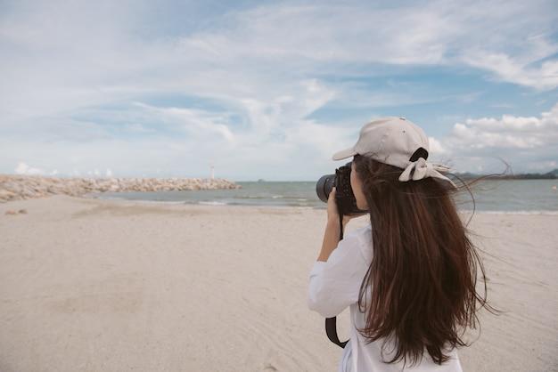 Fotógrafo fêmea asiático novo com câmera fora na praia em tailândia. mulher tailandesa, segurando a câmera na mão.