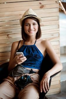 Fotógrafo fêmea moreno bonito novo que guarda o telefone, sorrindo.