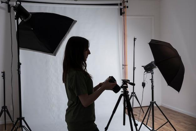 Fotógrafo fêmea no estúdio moderno da foto com equipamentos profissionais
