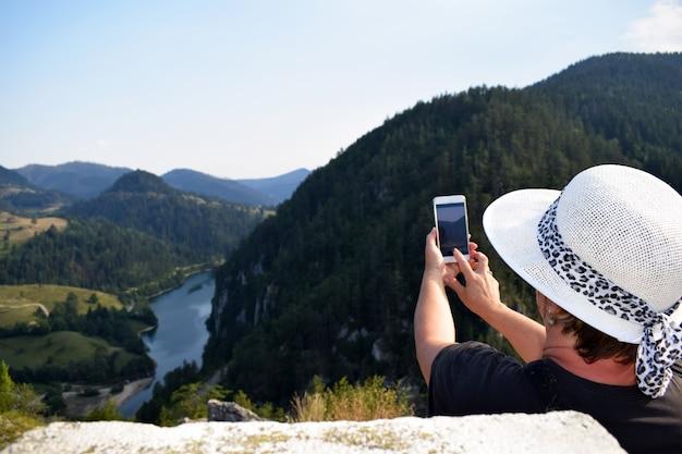 Fotógrafo fêmea que fotografa em um ajuste ao ar livre bonito.