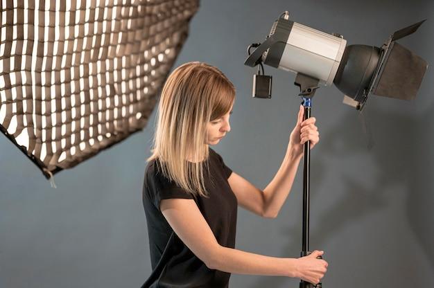 Fotógrafo feminino ajustando a lâmpada de estúdio