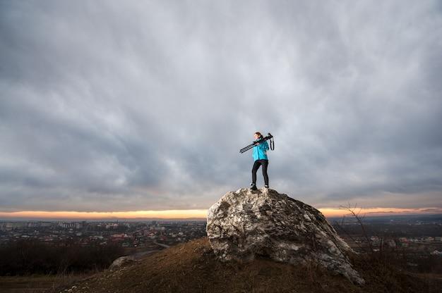 Fotógrafo feminino com câmera no tripé na grande rocha